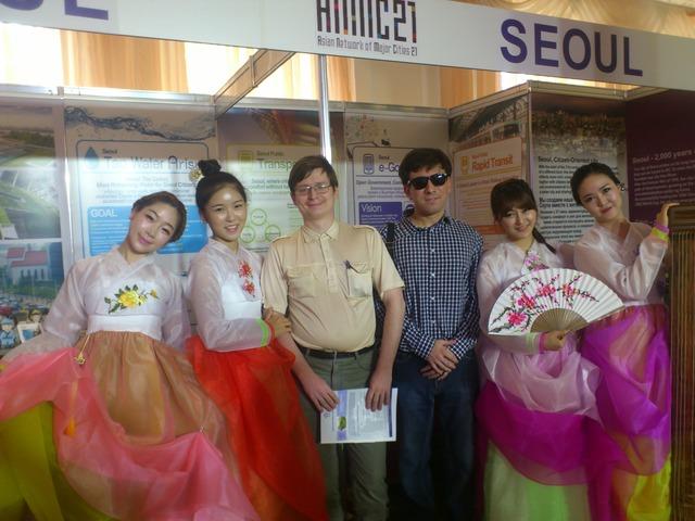 Два молодых человека стоят в группе кореянок в национальных одеждах