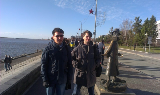 Фотография двух молодых людей на фоне памятника Чехову в Томске
