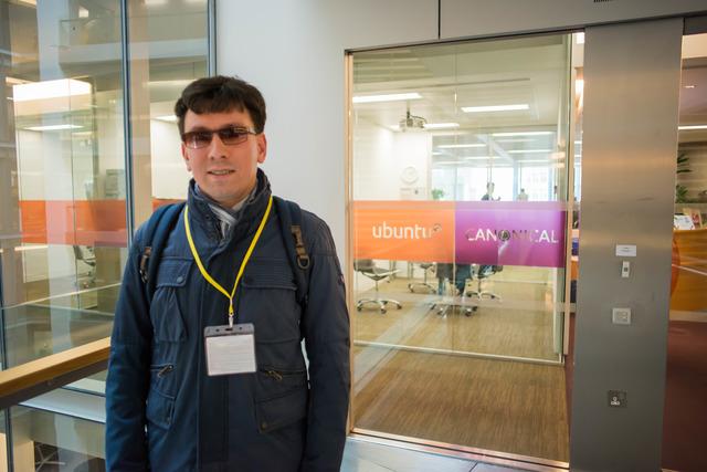 Фотография молодого человека на фоне  логотипа компании Canonical