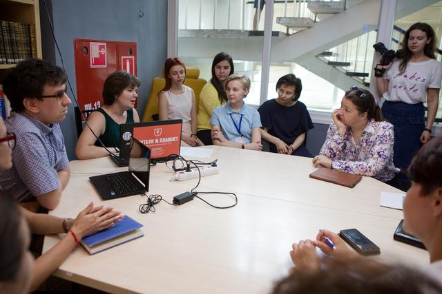 Группа людей беседует в помещении, сидя за столами